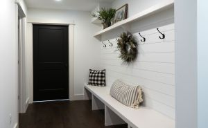 White bench with white wall planking and coat hooks