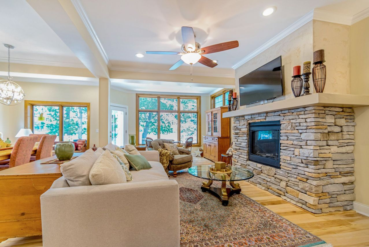 Stone fireplace with TV above flanks the right side of this lakefront living room.