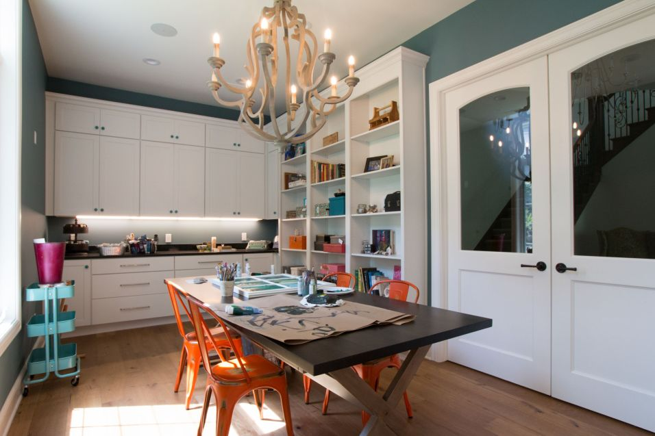 Dark wood craft table in room with white cabinets