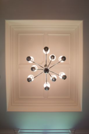 Chandelier hanging from wood trimmed tray ceiling
