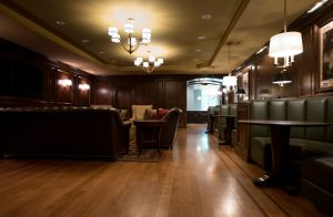 Wood floors with accent colors divide booths from main room with leather furniture