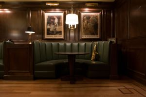 Green leather booth with War Bond posters on wall above