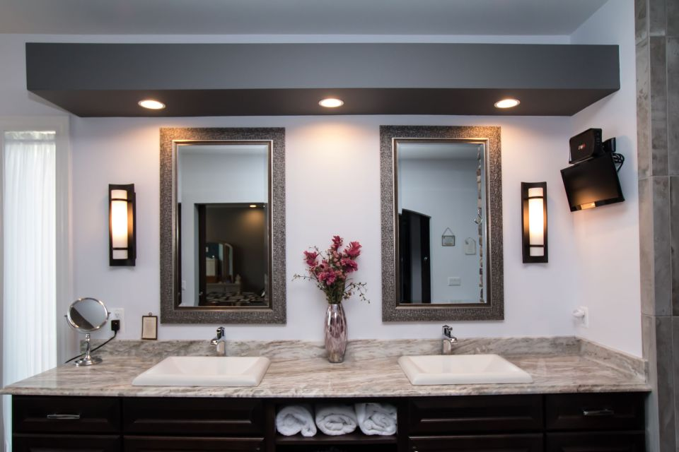 Granite counter with two sinks, wall mirrors and lighted soffit