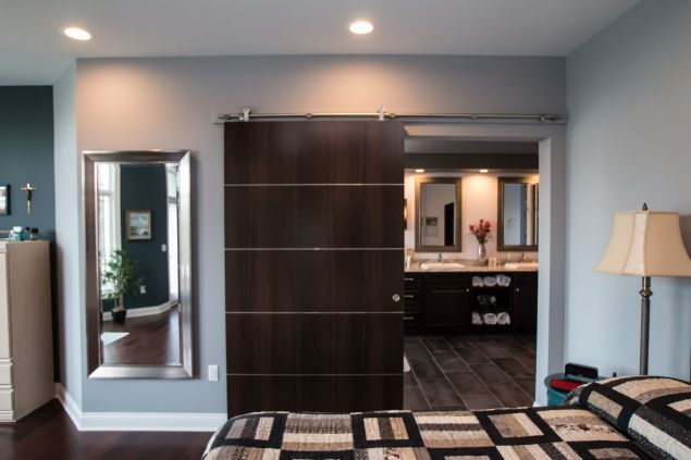 Dark wood barn door with horizontal chrome accents