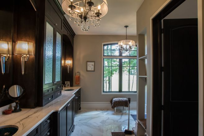 Dark wood cabinet flank the left side of this rich master bathroom