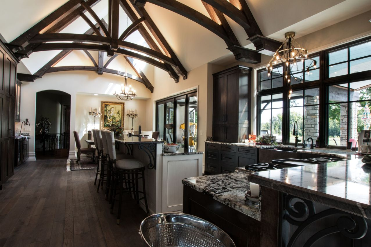 Dark wood kitchen cabinets with granite counters accent the timber trusses at the ceiling