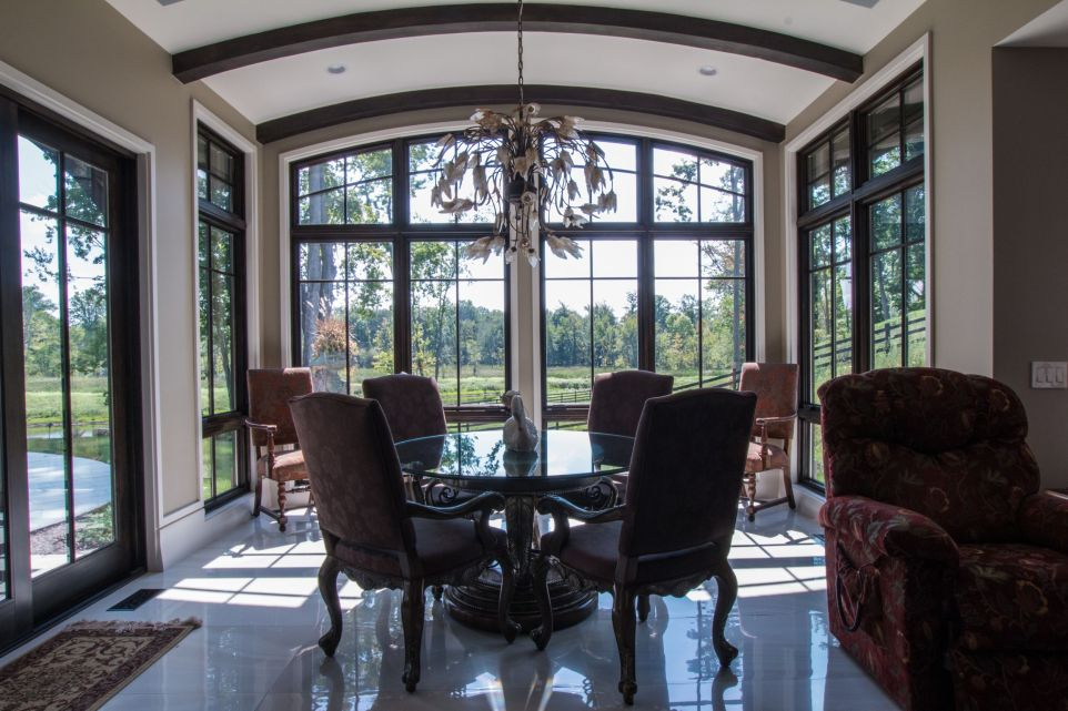 Luxurious table in glass sunroom with arched ceiling