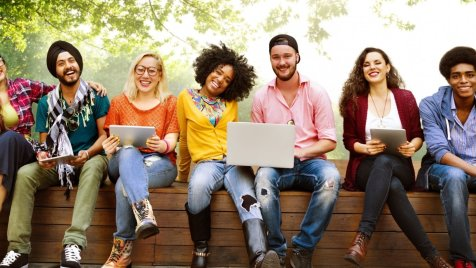 diverse group of happy college students sitting in a line, some with computers or tablets. Join an online college support group in Maryland to cope with the stress of COVID 19 at Montgomery County Counseling Center.