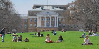 College Quad with students sitting outside on green grass.