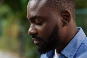 calm black man taking a deep breath. He gets adult therapy in Rockville, MD with one of the therapists from montgomery county counseling center