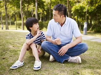 Asian father and son sitting outside taking