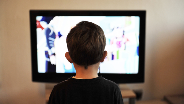 back of a young boy's head facing a tv depicting his screen addiction