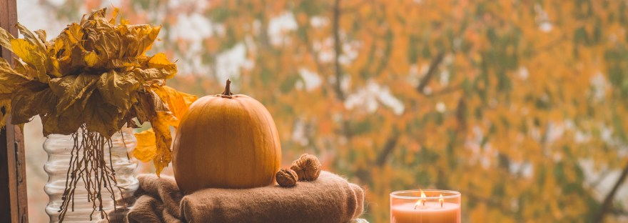fall windowscape with a pumpkin. blankets, and a candle