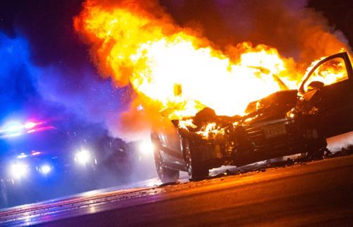 A car is on fire after an auto accident with a police officer arriving on the scene.