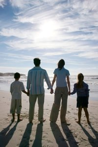 family of four holding hands on a beach