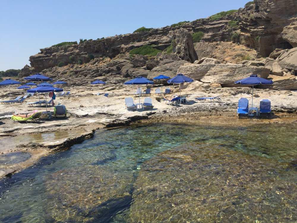 Kalithea et sa plage rocheuse. On retrouve chaises longues et parasols