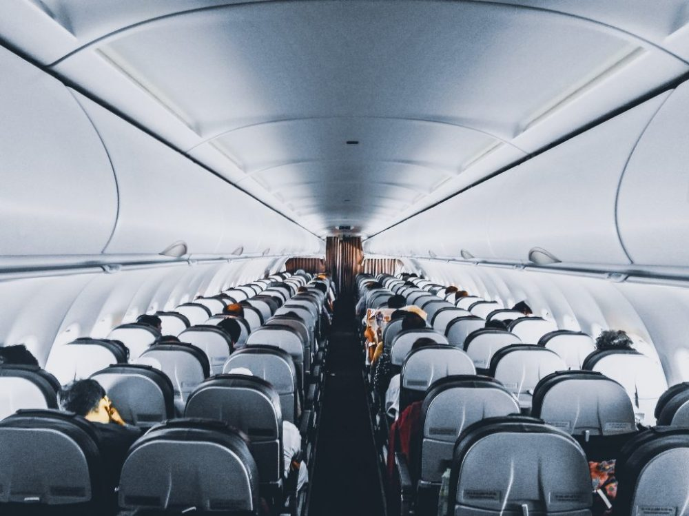 Intérieur d'un avion allée avec passagers crédit Pexels