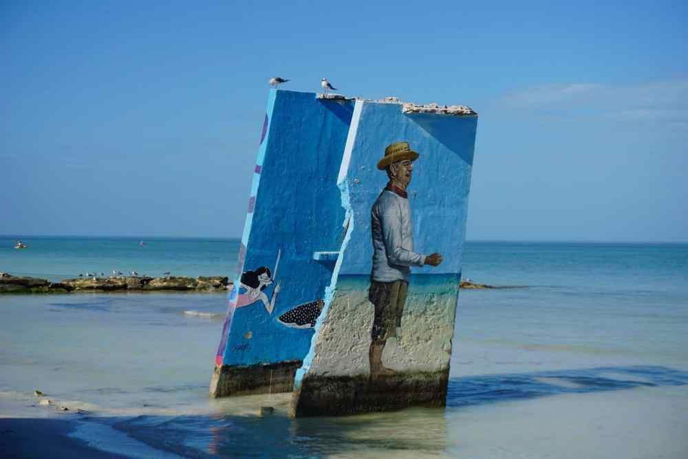Street art à Holbox, en bord de mer, le dessin d'un homme à chapeau les pieds dans l'eau. Mexique