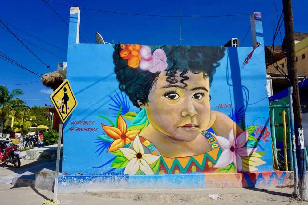 Street art d'une fillette sur mur bleu à Holbox, Mexique