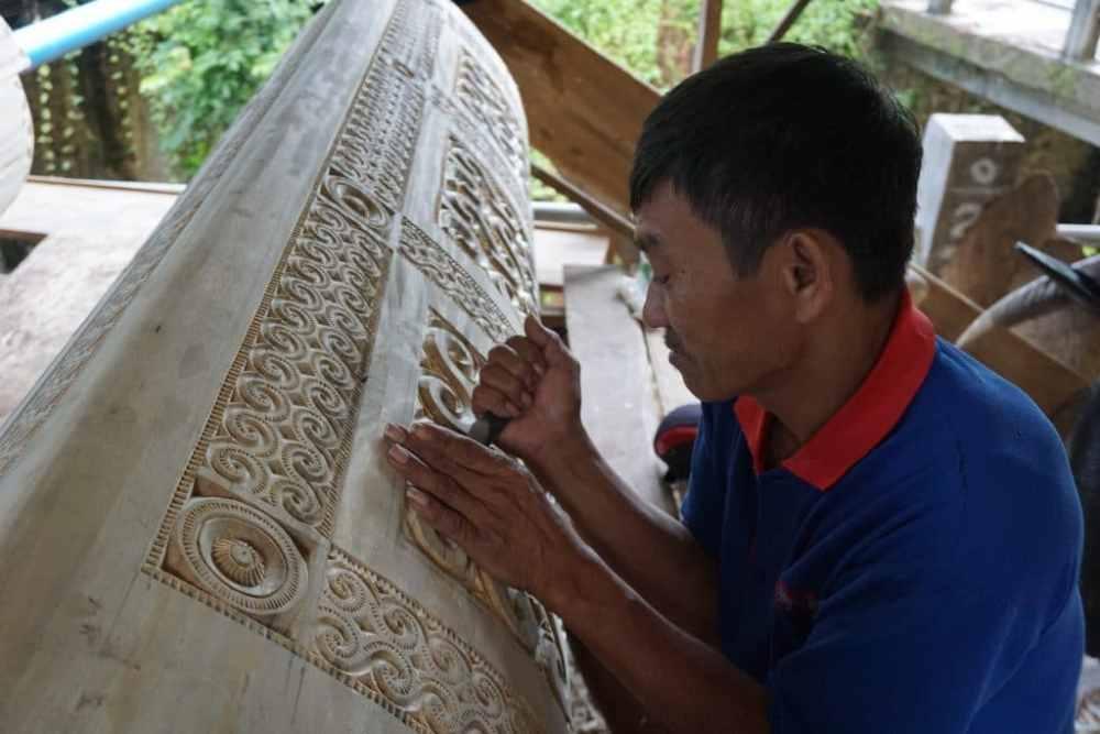 Un artiste sculpteur prépare un cercueil pour des funérailles dans le Toraja