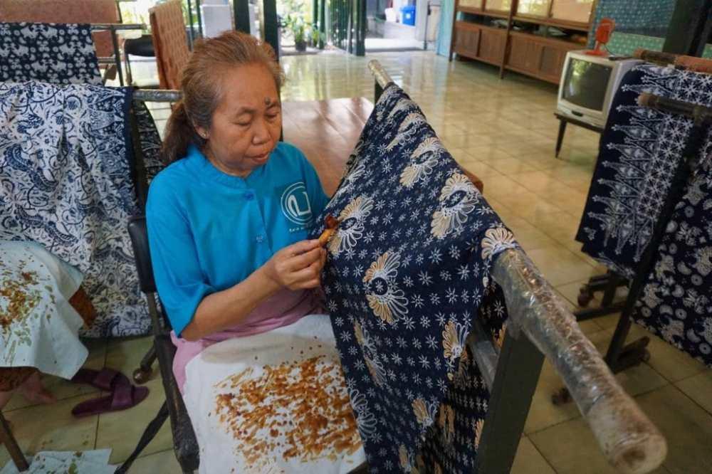 Une dame retire la cire d'un vêtement de Batik à la boutique Batik Winotosastro
