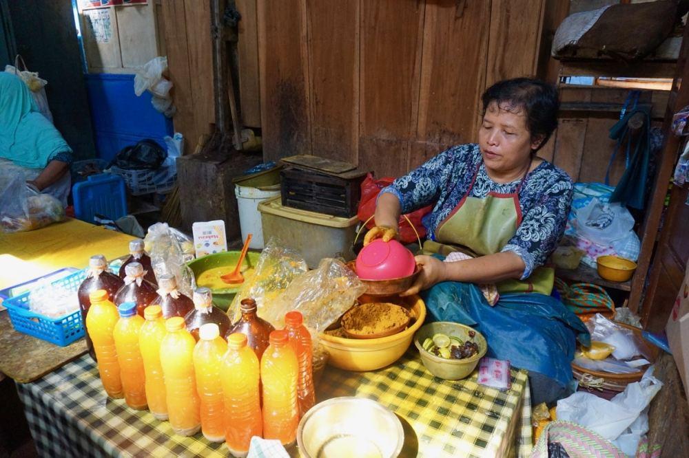 Une dame s'applique à préparer du Jamu à l'aide de différentes épices au marché de Kotagede à Jogja, Indonésie