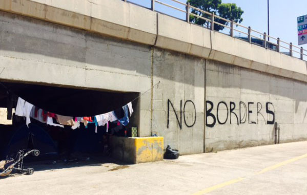 "overpass with ""no boarders"" written in spray paint, a laundry line, and a home to refugee families"