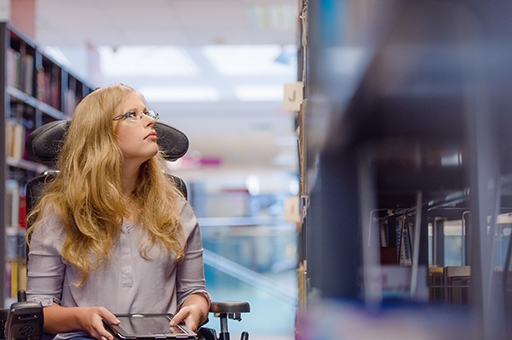 Young woman in wheelchair looking up for book in library