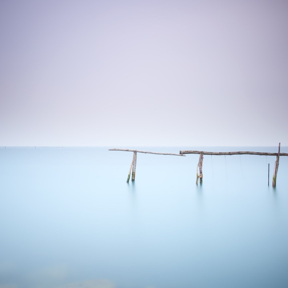 Poles and soft water on water landscape. Long exposure.