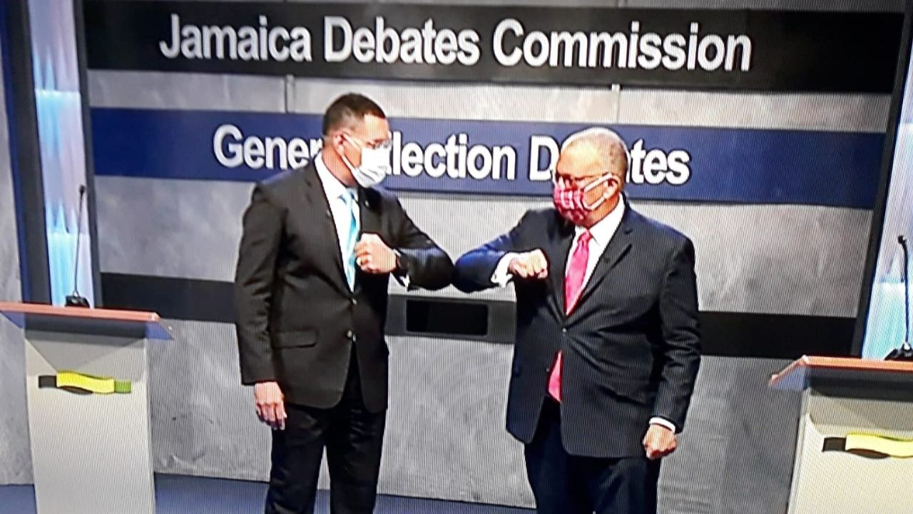Leaders of the JLP and PNP elbow bump