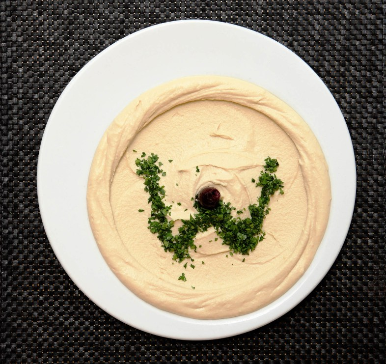 A plate of humus garnished with parsley and an olive from Shawarma King middle eastern grill at 5004 University Way Northeast.