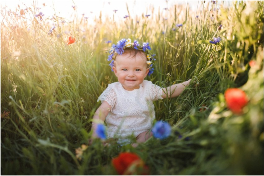 smiling baby girl with flower crown sitting in the field