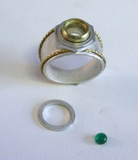 Starting on the ring. The green stone is an emerald.