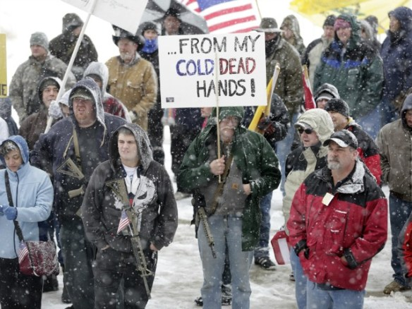 "Gun-rights activist Dave Larson, of Bountiful, Utah, carries his AR-15 rifle and a sign which reads, ""...From my cold, dead hands"" during a ""National Day of Resistance"" rally at the Utah State Capitol in Salt Lake City, Utah on Saturday, Feb. 23, 2013. Activists said they were were there to show their support for the U.S. Constitution and the 2nd Amendment. (AP Photo/Rick Bowmer)"