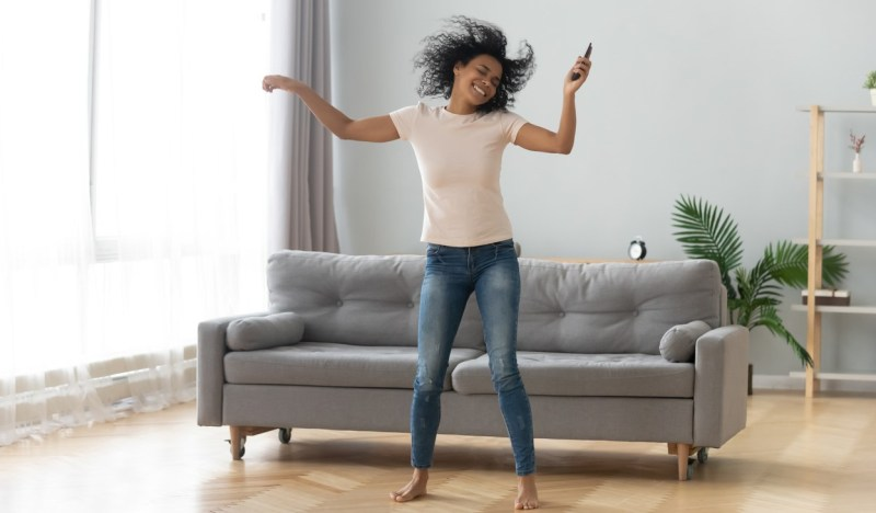 African woman dancing in living room at home