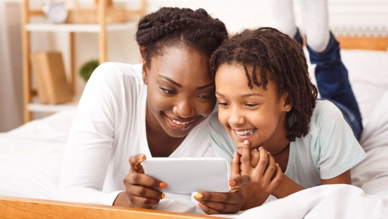 Smiling mother and daughter looking at a smart phone