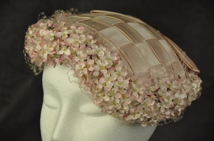 """016/017 Women's hat. Pale pink woven satin toque edged in small matching pink flowers under matching pink fascinator lace. Large pink, flat, satin bow at back of hat. Lined with satin lining material and labeled """"The TLB Hat""""."""