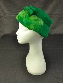 """Women's felt hat in emerald green """"styled by Michele"""" on label at back. Flatish style, with shallow crown wider brim. Well stitched matching band with bow at front and front of brim covered with matching emerald green feathers"""