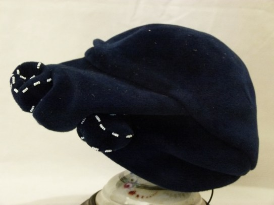 """016/022 Women's hat. Royal blue felted toque with molded crown and draped look molded brim wider at the front. Blue felt knotted bow edged with small white beads decorates the left centre of the brim at the front. Label reads """"Irene Wiener Original Model"""" . No lining just black grosgrain lining trim."""