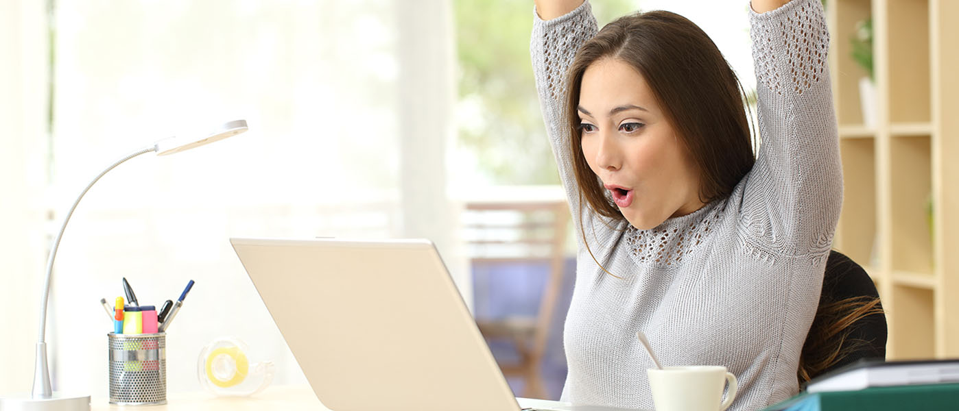 cheering woman working on laptop