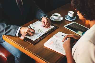 man and woman sitting in front of table with books and cup of coffee facing each other