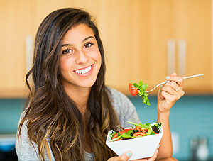 Portrait of beautiful young woman eating a bowl of healthy organic salad and smiling