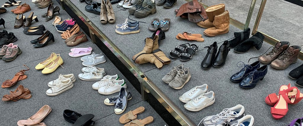A section of 111 pairs of shoes on a stage