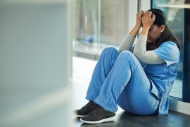 A woman in blue scrubs sits on the floor with her head in her hands