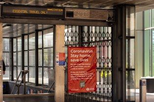 A red coronavirus poster warning people to stay at home is next to the entrance of a London underground