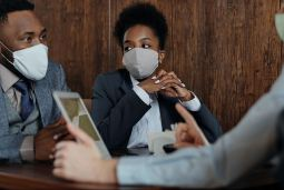Colleagues sat together around an iPad wearing masks