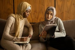 Two women in headscarves sit on a sofa and look at an iPad