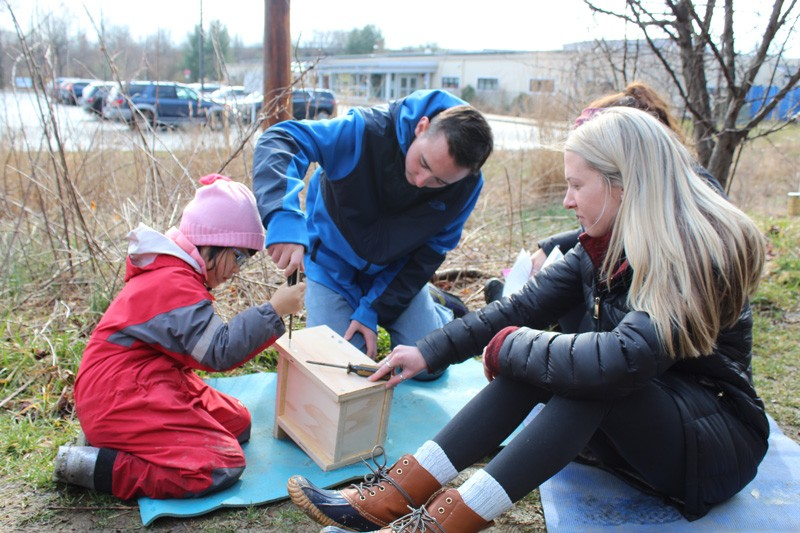 child building birdhouse with students