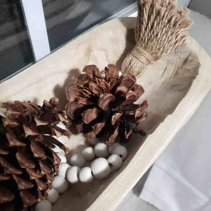 a wooden dough bowl full of pinecones and a Farmhouse Wooden Bead Garland