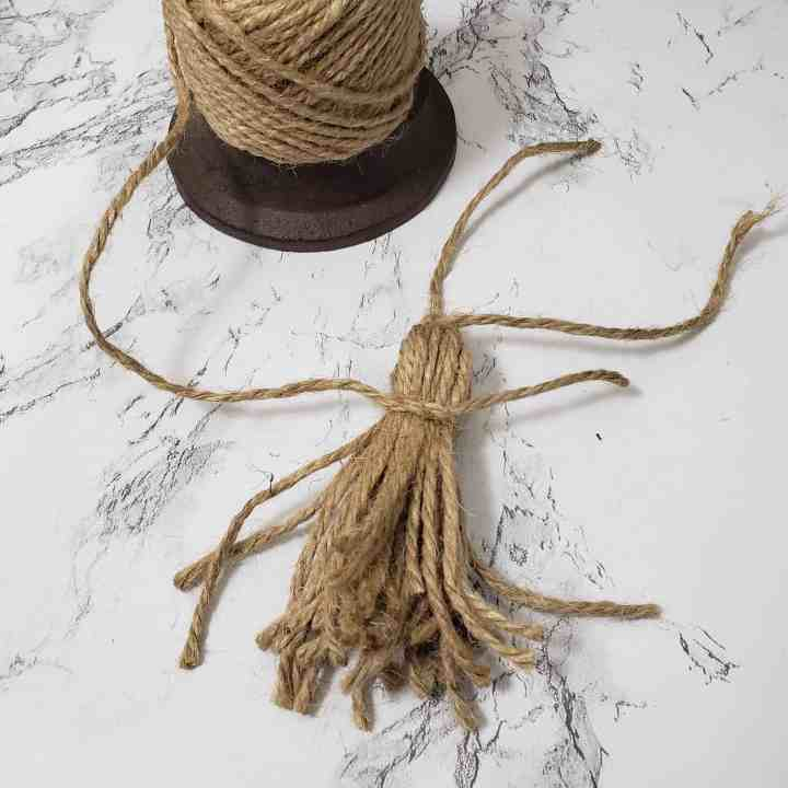 process photo of making a twine tassel for a Farmhouse Wooden Bead Garland